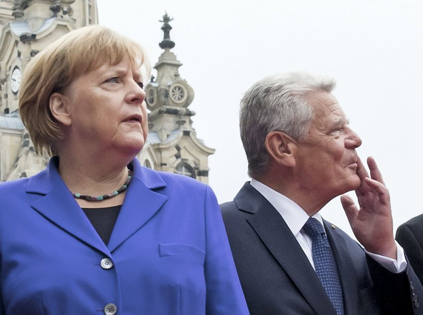 German Chancellor Angela Merkel stands besides German President Joachim Gauck prior the service in the Frauenkirche cathedral (Church of Our Lady) in Dresden, eastern Germany, Monday, Oct. 3, 2016. Germany celebrated the 26th anniversary of its reunification with festivals, concerts and parades across the country. (AP Photo/Jens Meyer)
